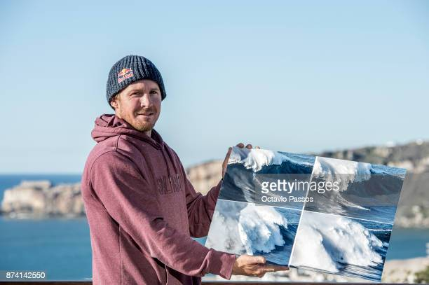 Andrew Cotton poses for the photograph holding the sequence of images of the wave that he surfed on November 8th at Praia do Norte at Nazare where he...
