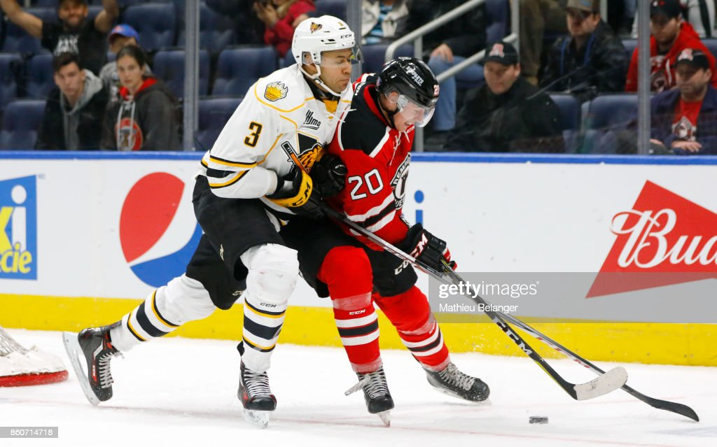 Andrew Coxhead #20 of the Quebec Remparts and Andrew Smith #3 of the Victoriaville Tigres battle for the puck during the third period of their QMJHL hockey game at the Centre Videotron on October 12, 2017 in Quebec City, Quebec, Canada.
