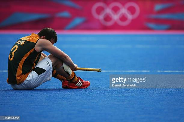 Andrew Cronje of South Africa sits on the pitch after losing 54 to Pakistan during the Men's Hockey match between Pakistan and South Africa on Day 9...