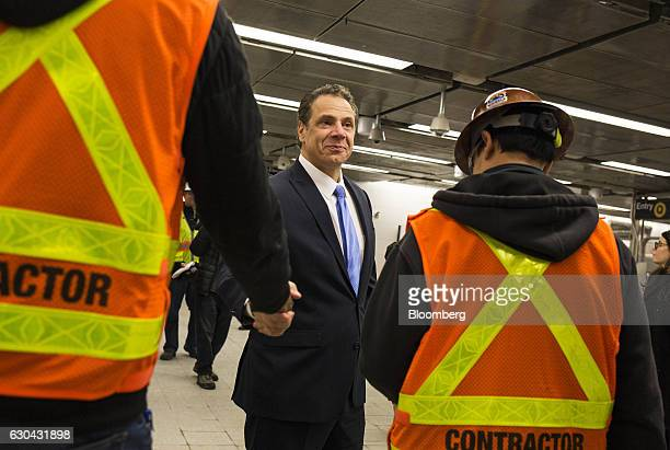 Andrew Cuomo governor of New York center shakes hands with construction workers while touring the 96th Street station of the new Second Avenue subway...