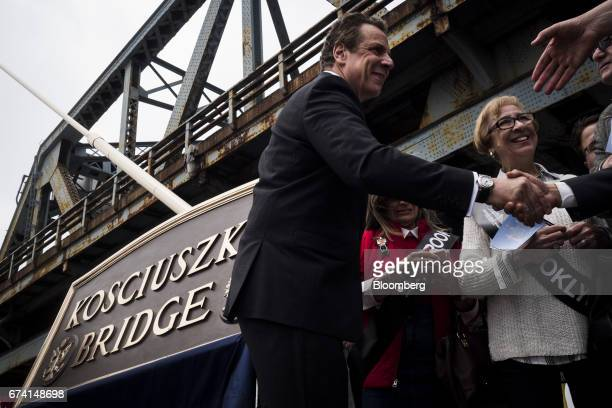 Andrew Cuomo governor of New York left shakes hands with attendees during the grand opening of the new Kosciuszko Bridge in the Brooklyn borough of...