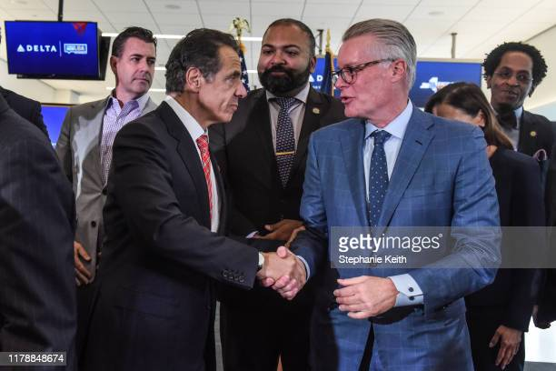Andrew Cuomo Governor of New York shakes hands with Ed Bastian CEO of Delta Airlines during an opening ceremony of Delta's new terminal at LaGuardia...