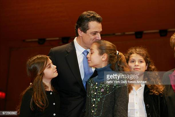 Andrew Cuomo kisses his daughter Mariah as daughters Michaela and Cara look on at during his swearingin ceremony as the 64th State Attorney General...