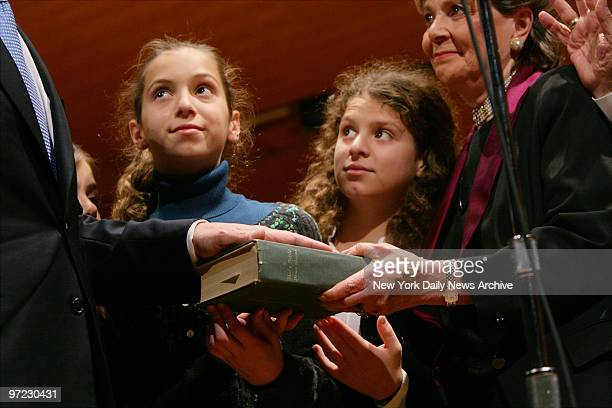 Andrew Cuomo's daughters Mariah and Cara look on as he swears his oath of office as the 64th State Attorney General on a bible held by his mother...