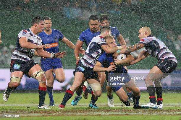 Andrew Deegan of the Force gets tackled by Tayler Adams and Billy Meakes of the Rebels during the World Series Rugby match between the Force and the...