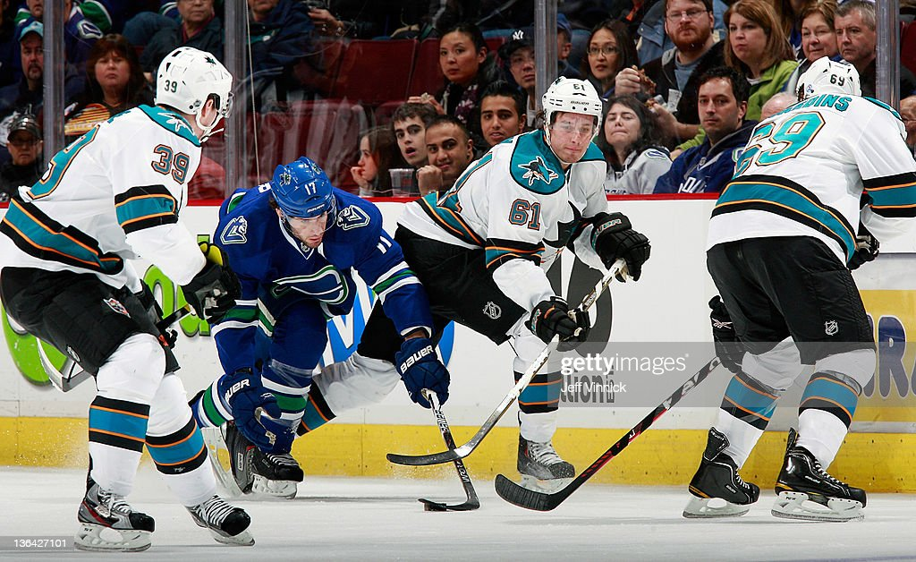 Andrew Desjardins #69, Logan Couture #39 and Justin Braun #61 of the San Jose Sharks look on as Ryan Kesler #17 of the Vancouver Canucks steals the puck during their NHL game at Rogers Arena January 2, 2012 in Vancouver, British Columbia, Canada.