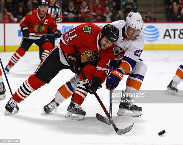 Andrew Desjardins of the Chicago Blackhawks and Anders Lee of the New York Islanders battle for the puck at the United Center on March 3 2017 in...