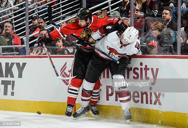 Andrew Desjardins of the Chicago Blackhawks and Connor Murphy of the Arizona Coyotes get physical by the boards in the first period of the NHL game...