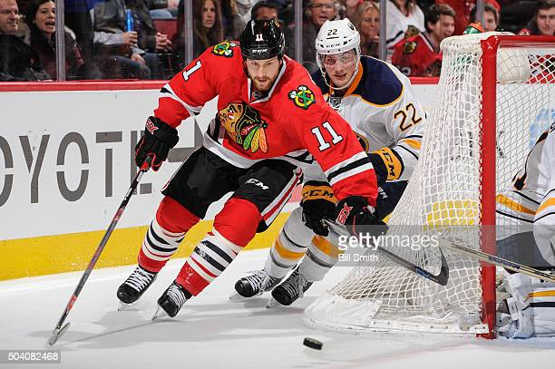 Andrew Desjardins of the Chicago Blackhawks and Johan Larsson of the Buffalo Sabres chase the puck around the net in the second period of the NHL...