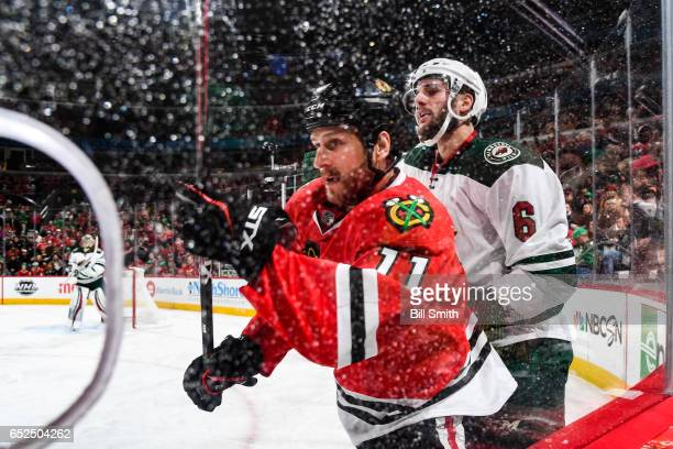 Andrew Desjardins of the Chicago Blackhawks and Marco Scandella of the Minnesota Wild skate around the boards in the first period at the United...