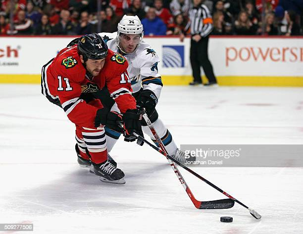 Andrew Desjardins of the Chicago Blackhawks battles for the puck with Dylan DeMelo of the San Jose Sharks at the United Center on February 9 2016 in...