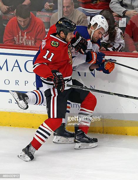 Andrew Desjardins of the Chicago Blackhawks checks Luke Gazdic of the Edmonton Oilers into the boards at the United Center on March 6 2015 in Chicago...