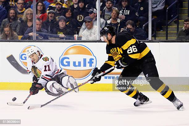 Andrew Desjardins of the Chicago Blackhawks falls while battling for a loose puck against Kevan Miller of the Boston Bruins during the second period...