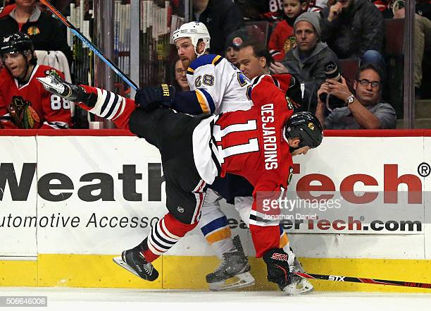 Andrew Desjardins of the Chicago Blackhawks gets dumped to the ice by Kyle Brodziak of the St Louis Blues at the United Center on January 24 2016 in...