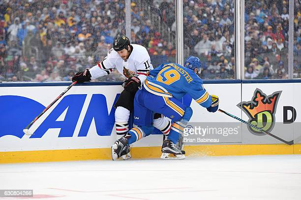 Andrew Desjardins of the Chicago Blackhawks is hit by Jay Bouwmeester of the St Louis Blues during the 2017 Bridgestone NHL Winter Classic at Busch...