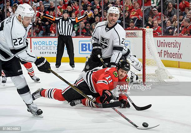 Andrew Desjardins of the Chicago Blackhawks reaches for the puck against Trevor Lewis and Alec Martinez of the Los Angeles Kings in the first period...