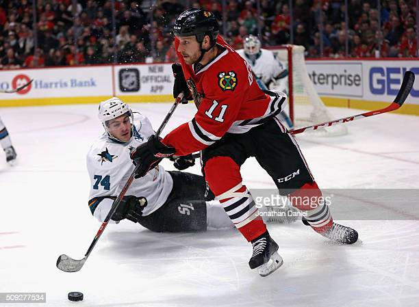 Andrew Desjardins of the Chicago Blackhawks turns to pass as Dylan DeMelo of the San Jose Sharks slips and hits the ice at the United Center on...