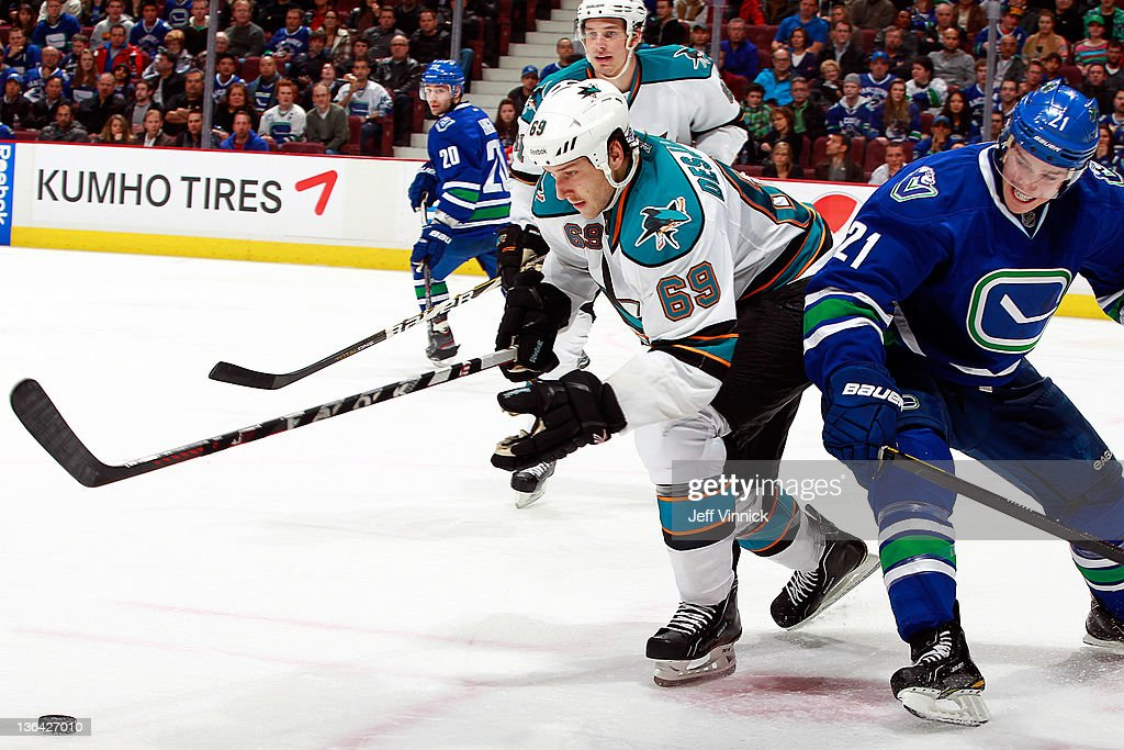 Andrew Desjardins #69 of the San Jose Sharks and Mason Raymond #21 of the Vancouver Canucks battle for a loose puck during their NHL game at Rogers Arena January 2, 2012 in Vancouver, British Columbia, Canada.