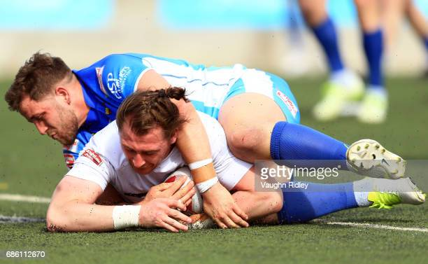 Andrew Dixon of Toronto Wolfpack scores a try as he is tackled by Lewis Charnock of Barrow Raiders in the first half of a Kingstone Press League 1...