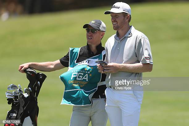 Andrew Dodt of Australia and his caddie Tom Davis talk during day one of the 2016 Australian PGA Championship at RACV Royal Pines Resort on December...