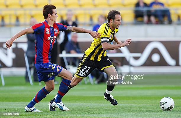 Andrew Durante of the Phoenix runs the ball under pressure from Ryan Griffiths of the Jets during the round 12 ALeague match between Wellington...