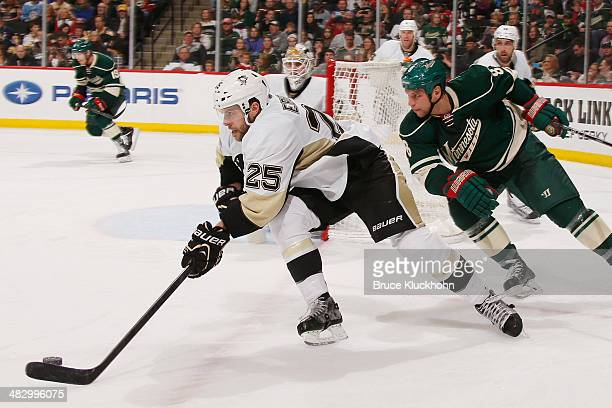 Andrew Ebbett of the Pittsburgh Penguins skates with the puck while Cody McCormick of the Minnesota Wild defends during the game on April 5 2014 at...