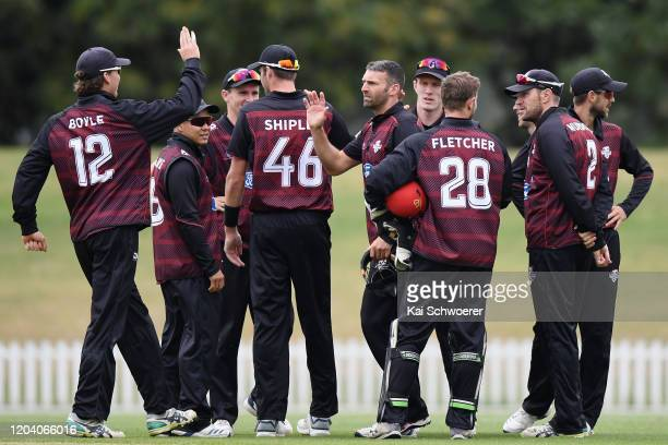 Andrew Ellis of Canterbury is congratulated by team mates after dismissing Mitch Renwick of Otago during the Ford Trophy match between Canterbury and...