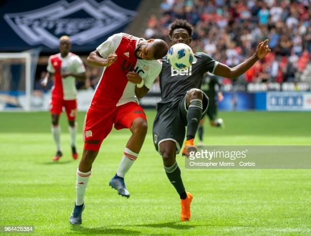 Andrew Farrell of the New England Revolution and Alphonso Davies of the Vancouver Whitecaps compete for the ball at BC Place on May 26 2018 in...