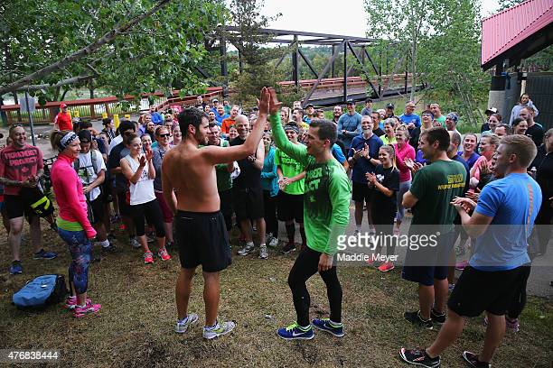 Andrew Ference captain of the Edmonton Oilers high fives a participant during a November Project workout at Louise McKinney Riverfront Park on June...