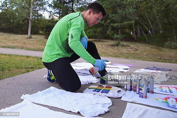 Andrew Ference captain of the Edmonton Oilers spray paints shirts during a November Project workout at Louise McKinney Riverfront Park on June 12...