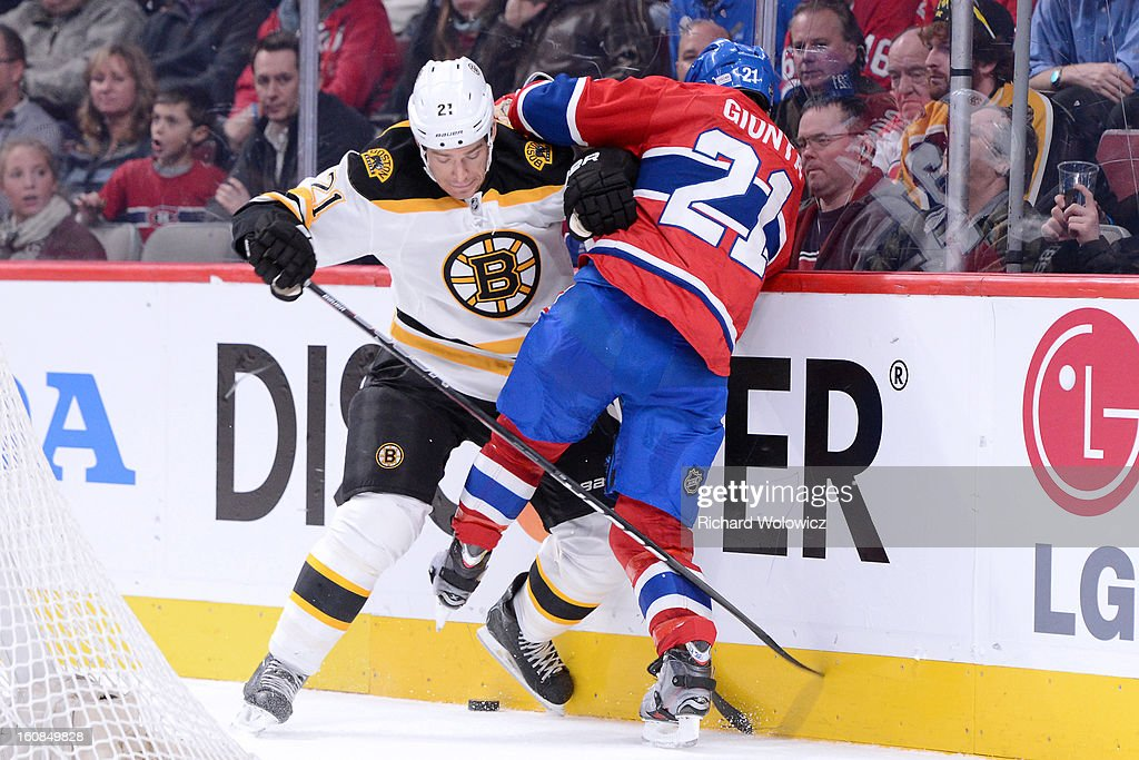 Andrew Ference #21 of the Boston Bruins and Brian Gionta #21 of the Montreal Canadiens battle for the puck during the NHL game at the Bell Centre on February 6, 2013 in Montreal, Quebec, Canada. The Bruins defeated the Canadiens 2-1.