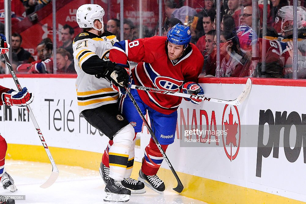 Andrew Ference #21 of the Boston Bruins body checks Brandon Prust #8 of the Montreal Canadiens during the NHL game at the Bell Centre on April 6, 2013 in Montreal, Quebec, Canada. The Canadiens defeated the Bruins 2-1.