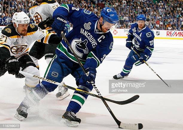 Andrew Ference of the Boston Bruins checks Henrik Sedin of the Vancouver Canucks during Game One of 2011 NHL Stanley Cup Finals at Rogers Arena on...