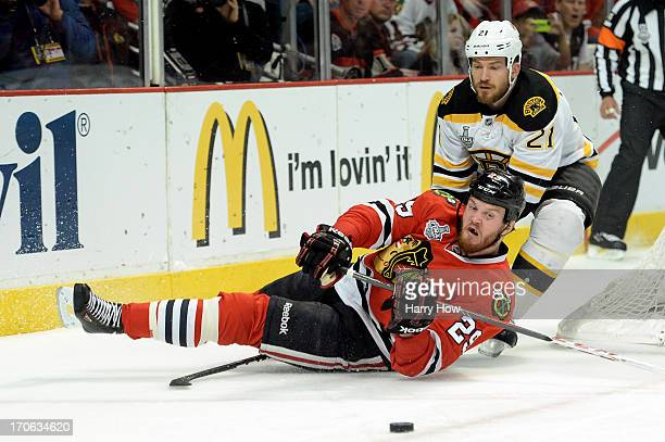 Andrew Ference of the Boston Bruins is called for a tripping penalty in the first period against Bryan Bickell of the Chicago Blackhawks in Game Two...