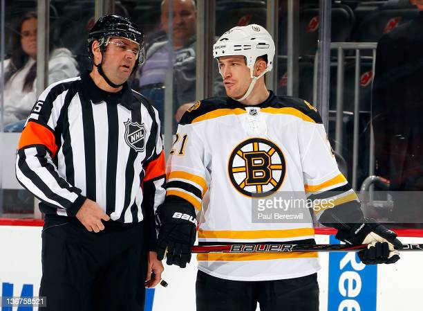 Andrew Ference of the Boston Bruins talks with referee Stephane Auger during an NHL hockey game against the New Jersey Devils at Prudential Center on...