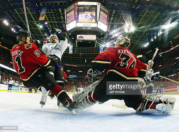 Andrew Ference of the Calgary Flames is hit in front of the net by Cory Stillman of the Tampa Bay Lightning as goaltender Miikka Kiprusoff defends...