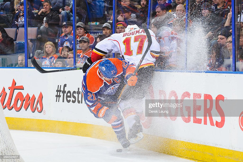 Andrew Ference #21 of the Edmonton Oilers checks Lance Bouma #17 of the Calgary Flames during an NHL game at Rexall Place on December 7, 2013 in Edmonton, Alberta, Canada. The Flames defeated the Oilers 2-1 in overtime.