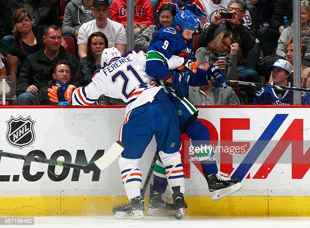 Andrew Ference of the Edmonton Oilers checks Zack Kassian of the Vancouver Canucks into the boards during their NHL game at Rogers Arena October 11...