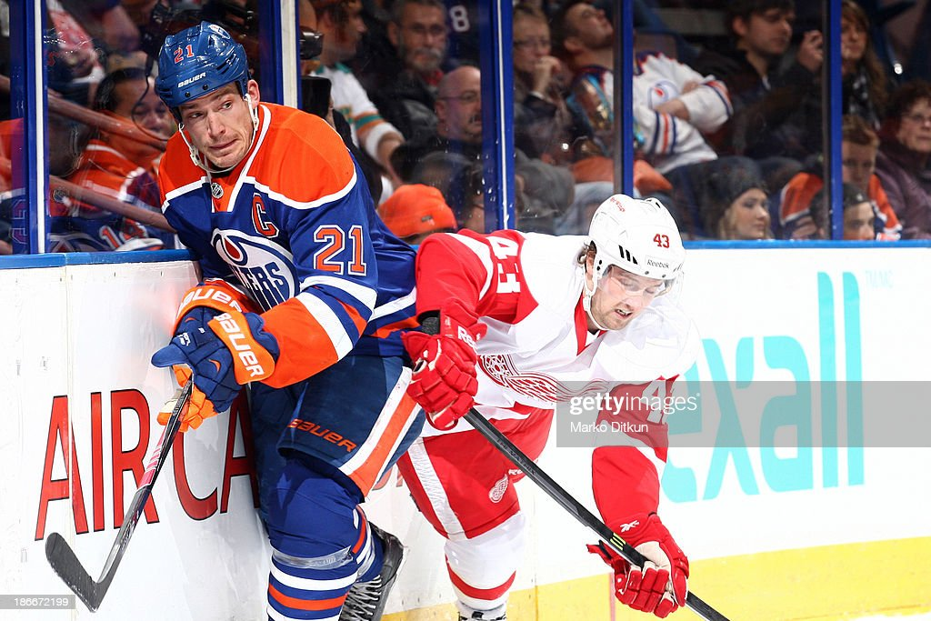 Andrew Ference #21 of the Edmonton Oilers evades a hit from Darren Helm #43 of the Detroit Red Wings on November 2, 2013 at Rexall Place in Edmonton, Alberta, Canada.