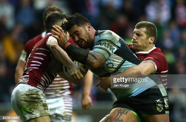 Andrew Fifita of CronullaSutherland Sharks is tackled by Tony Clubb and Morgan Escare of Wigan Warriors during the Dacia World Club Challenge match...