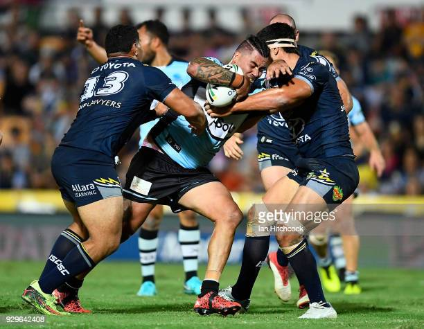 Andrew Fifita of the Sharks is tackled by Jason Taumalolo and Jordan McLean of the Cowboys during the round one NRL match between the North...
