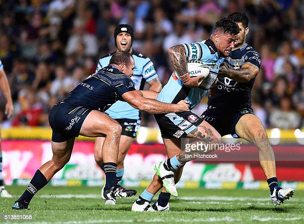 Andrew Fifita of the Sharks is tackled by Matthew Scott and James Tamou of the Cowboys during the round one NRL match between the North Queensland...