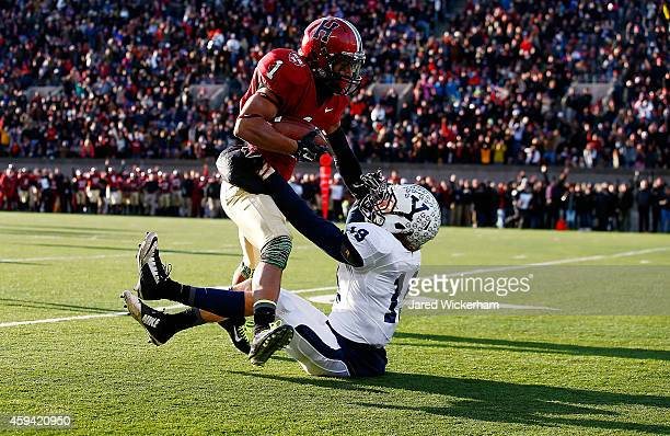 Andrew Fischer of the Harvard Crimson catches a pass in front of Jason Alessi of the Yale Bulldogs before running into the endzone for a touchdown...