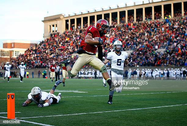 Andrew Fischer of the Harvard Crimson leaps into the endzone for the gamewinning touchdown in the fourth quarter in front of Cole Champion of the...