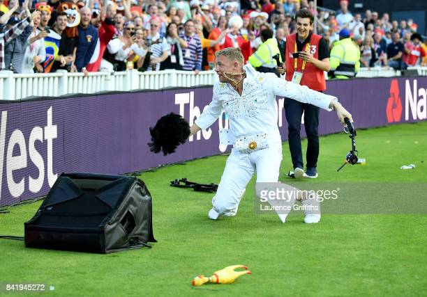 Andrew Flintoff falls over a speaker as he performs as Elvis Presley during the NatWest T20 Blast Final between Birmingham Bears and Notts Outlaws at...