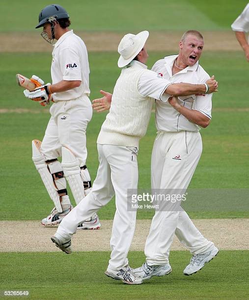 Andrew Flintoff of England celebrates the wicket of Adam Gilchrist of Australia with captain Michael Vaughan during day one of the first npower Ashes...