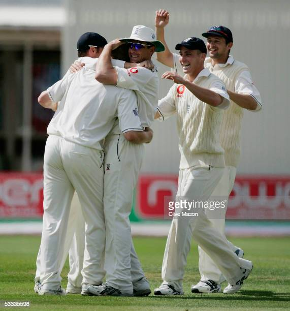 Andrew Flintoff of England is congratulated by his team mates after taking the wicket of Shane Warne of Australia during day four of the second...
