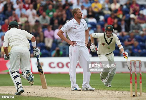 Andrew Flintoff of England looks dejected as Michael Clarke and Marcus North of Australia run between the wickets during day three of the npower 1st...