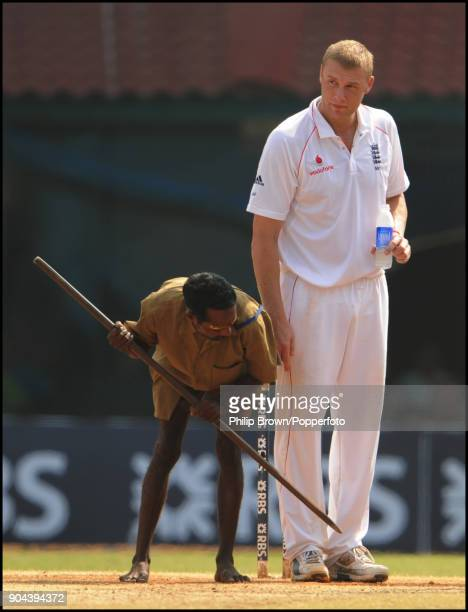 Andrew Flintoff of England watches as a groundsman works on the bowlers' footmarks during the 1st Test match between India and England at MA...