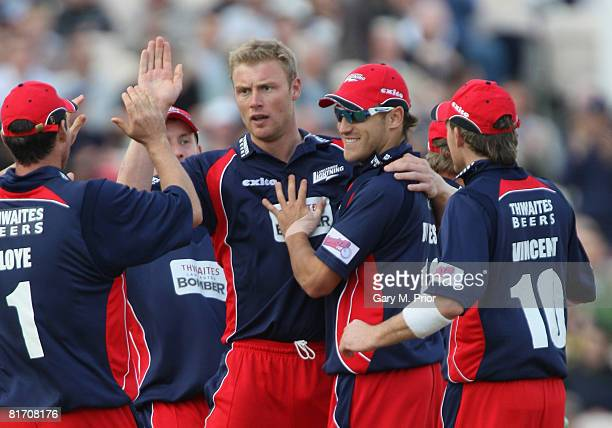 Andrew Flintoff of Lancashire is congratulated by his team mates after taking the wicket of Adam Voges during the Twenty20 Cup match between...